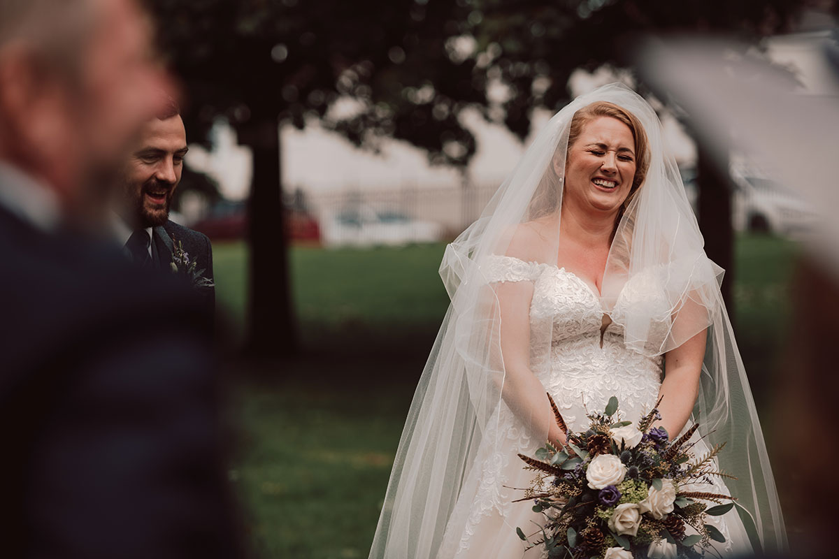 bride laughing during wedding ceremony on Glasgow Green