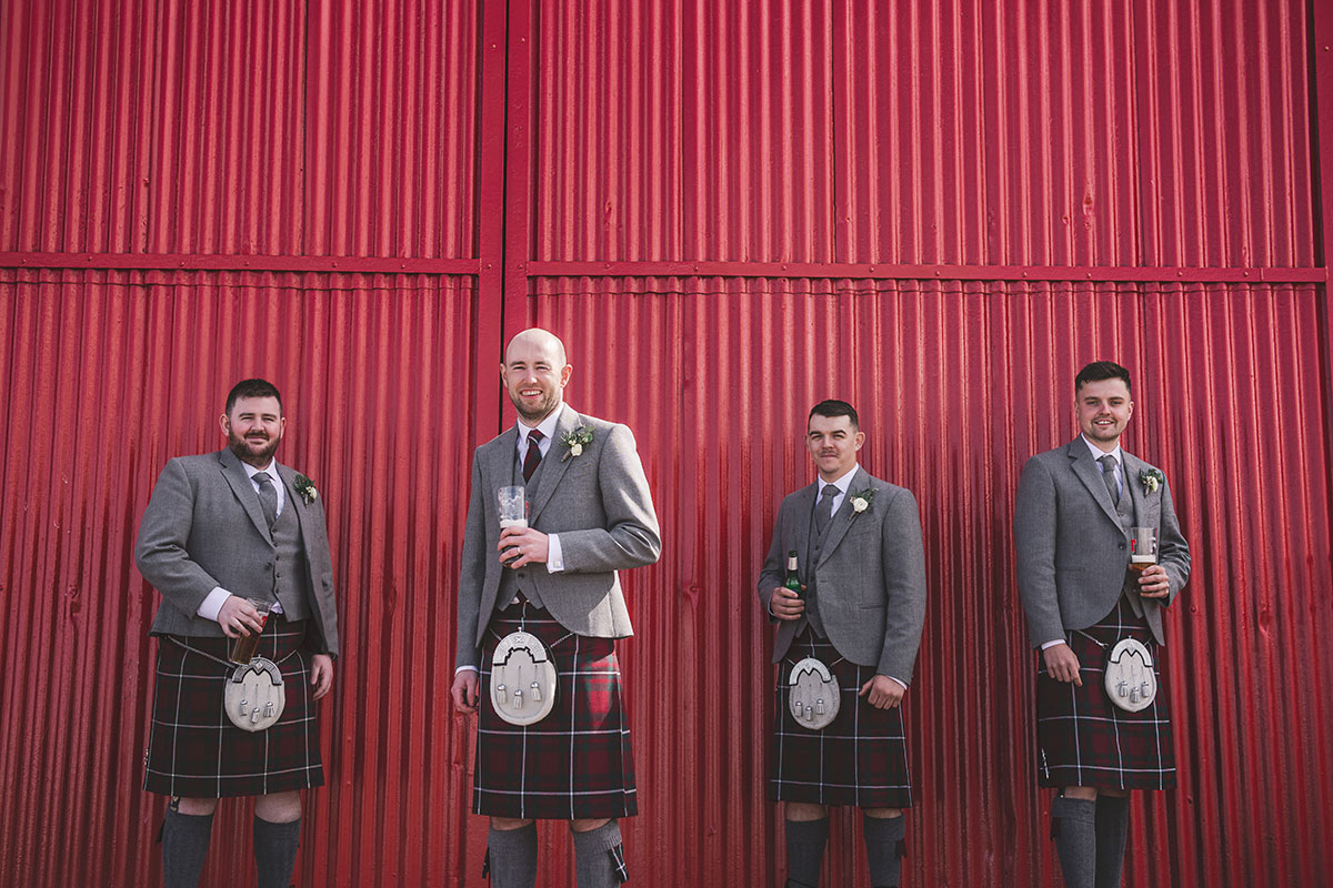 four men wearing kilts and carrying beer posing at red doors at Kinkell Byre