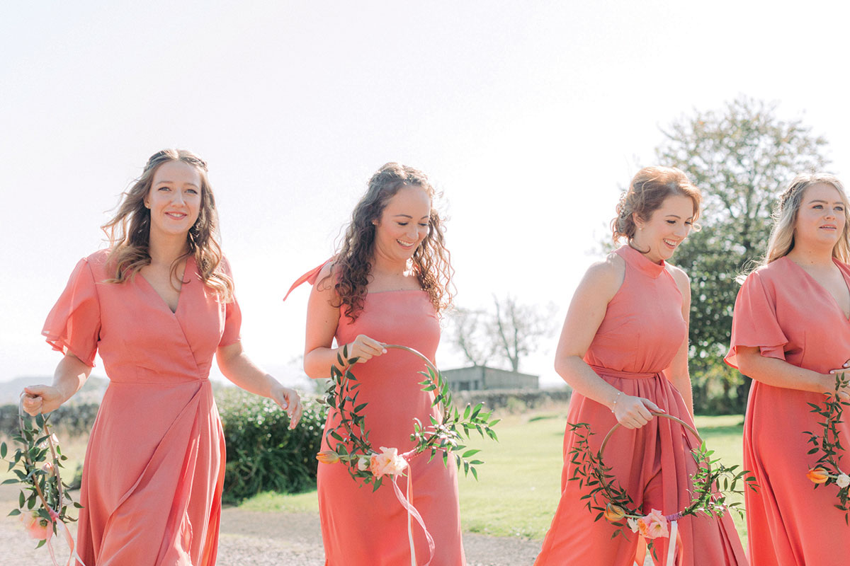 four women walking outside wearing coral Rewritten bridesmaids dresses and carrying floral hoop