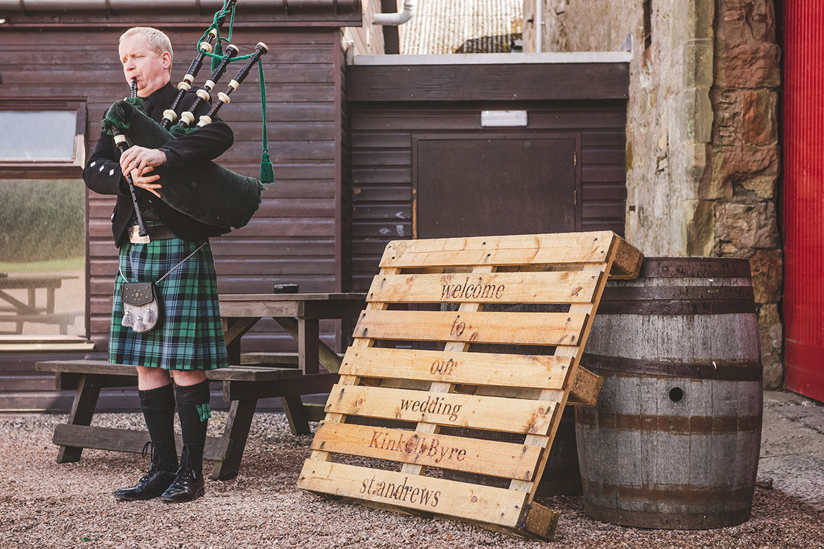 a piper playing outside Kinkell Byre with wooden welcome to our wedding pallet