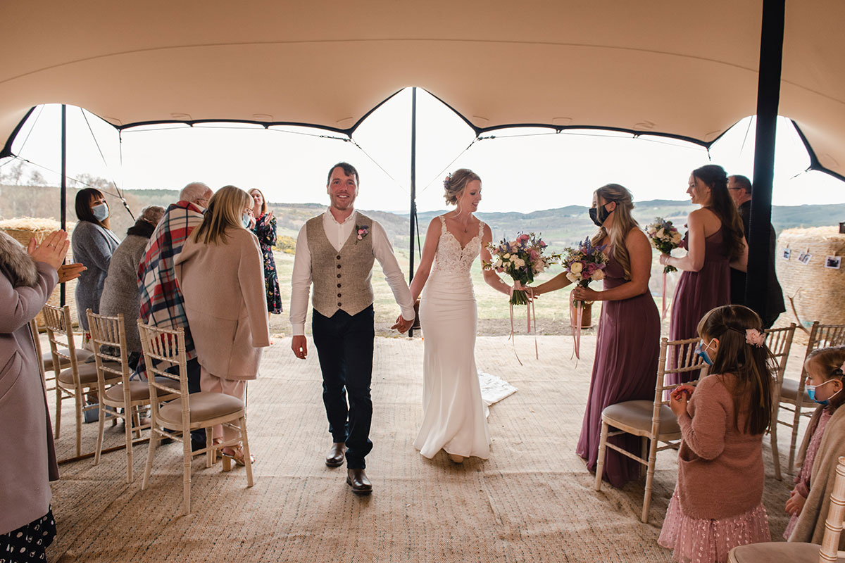 bride and groom leaving wedding tent with socially distanced wedding guests