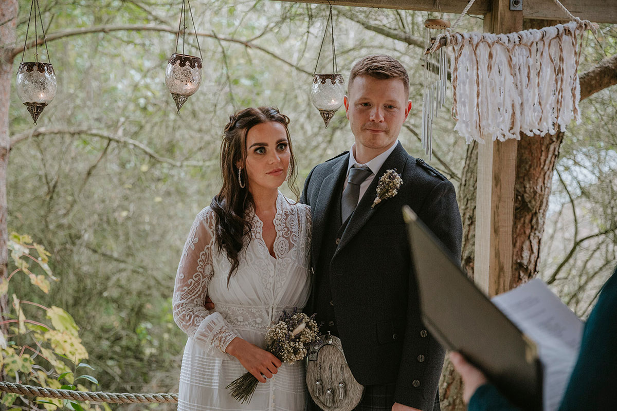 bride and groom listening to registrar during wedding ceremony at Roulotte Retreat