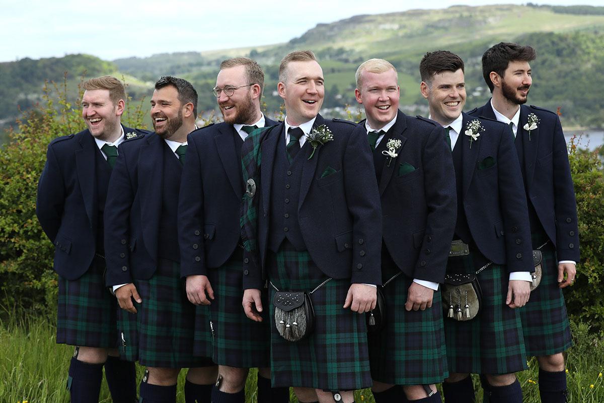 seven men in kilts posing against hills in Scotland