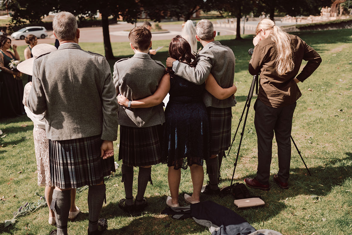 the back of guests hugging while watching a wedding ceremony happen on Glasgow Green