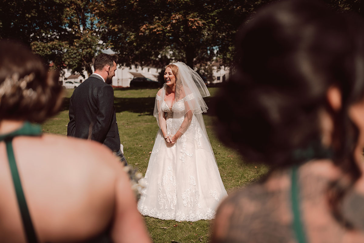 a bride and groom laughing during a wedding ceremony on Glasgow Green
