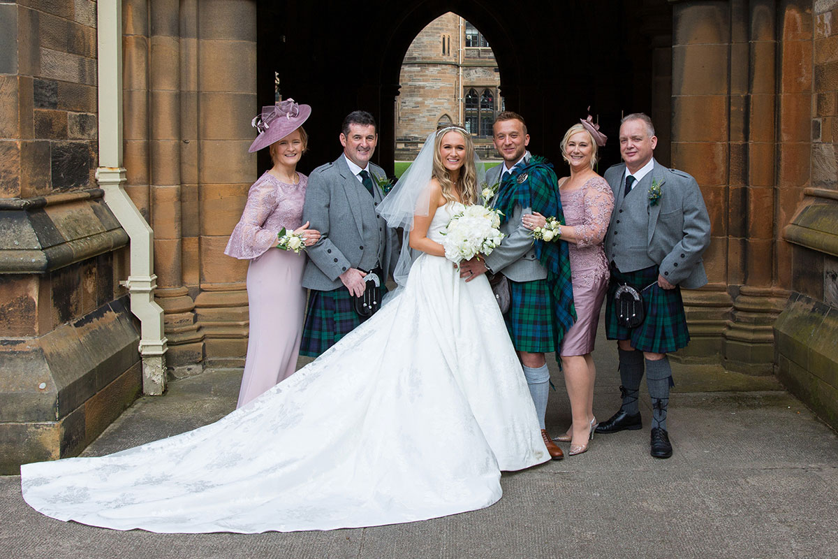 bride and groom posing with family outside Glasgow University Memorial Chapel