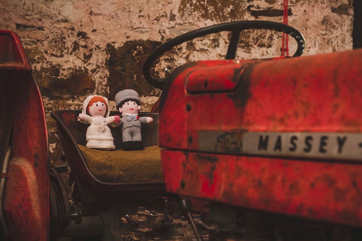 knitted bride and groom figures sitting on a Massey Fergusson tractor