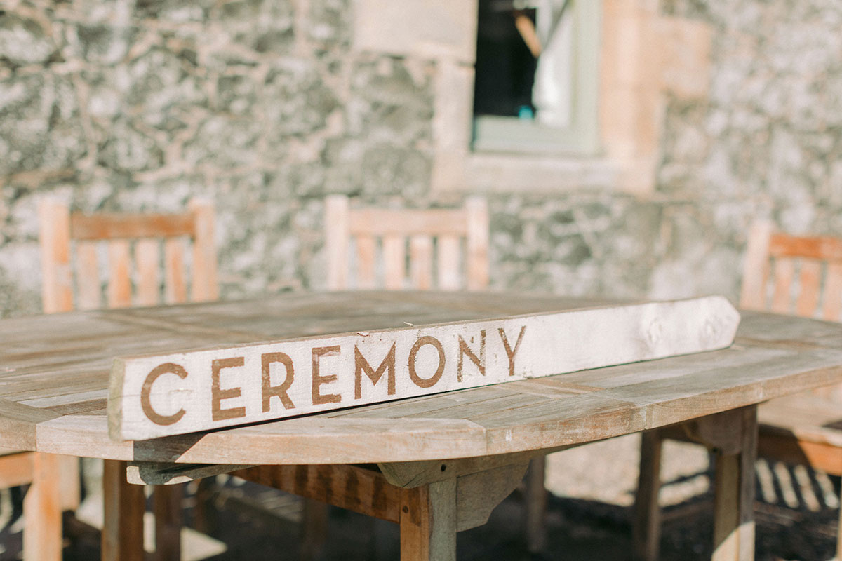 wooden ceremony sign sitting on a wooden table