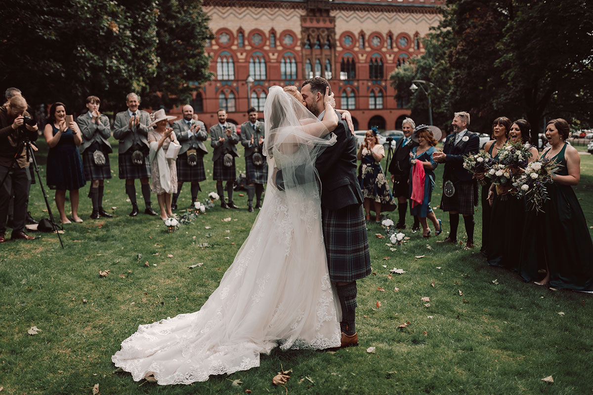 a bride and groom kissing watched on by guests outside WEST on the Green at Glasgow Green