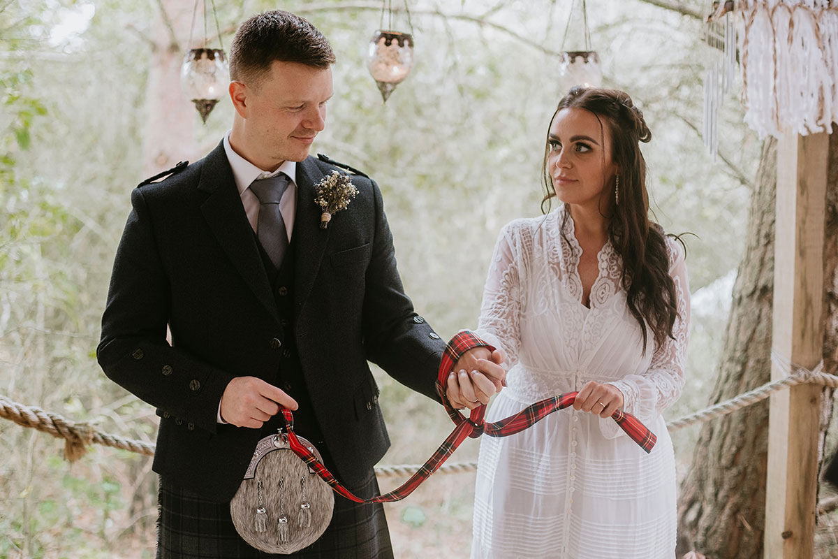 bride and groom performing handfasting ceremony