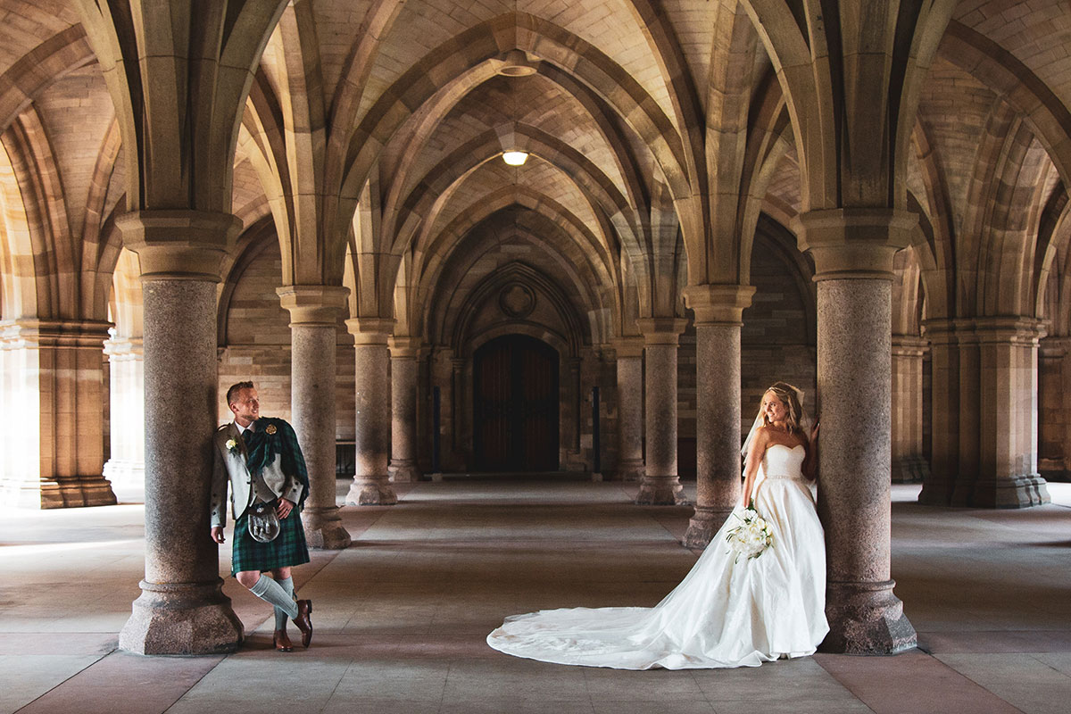bride and groom posing in the cloisters at Glasgow University
