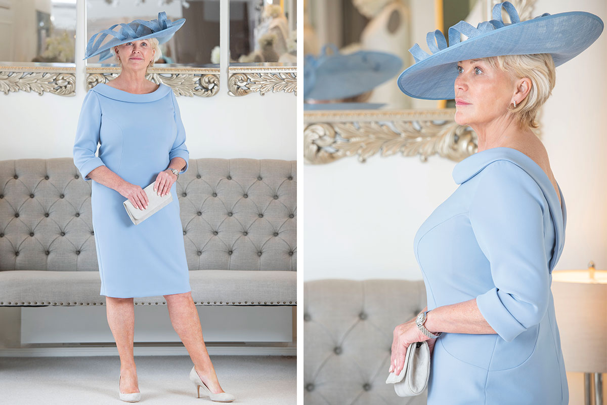A lady wearing a duck egg blue dress and hat from Joyce Young Design Studios