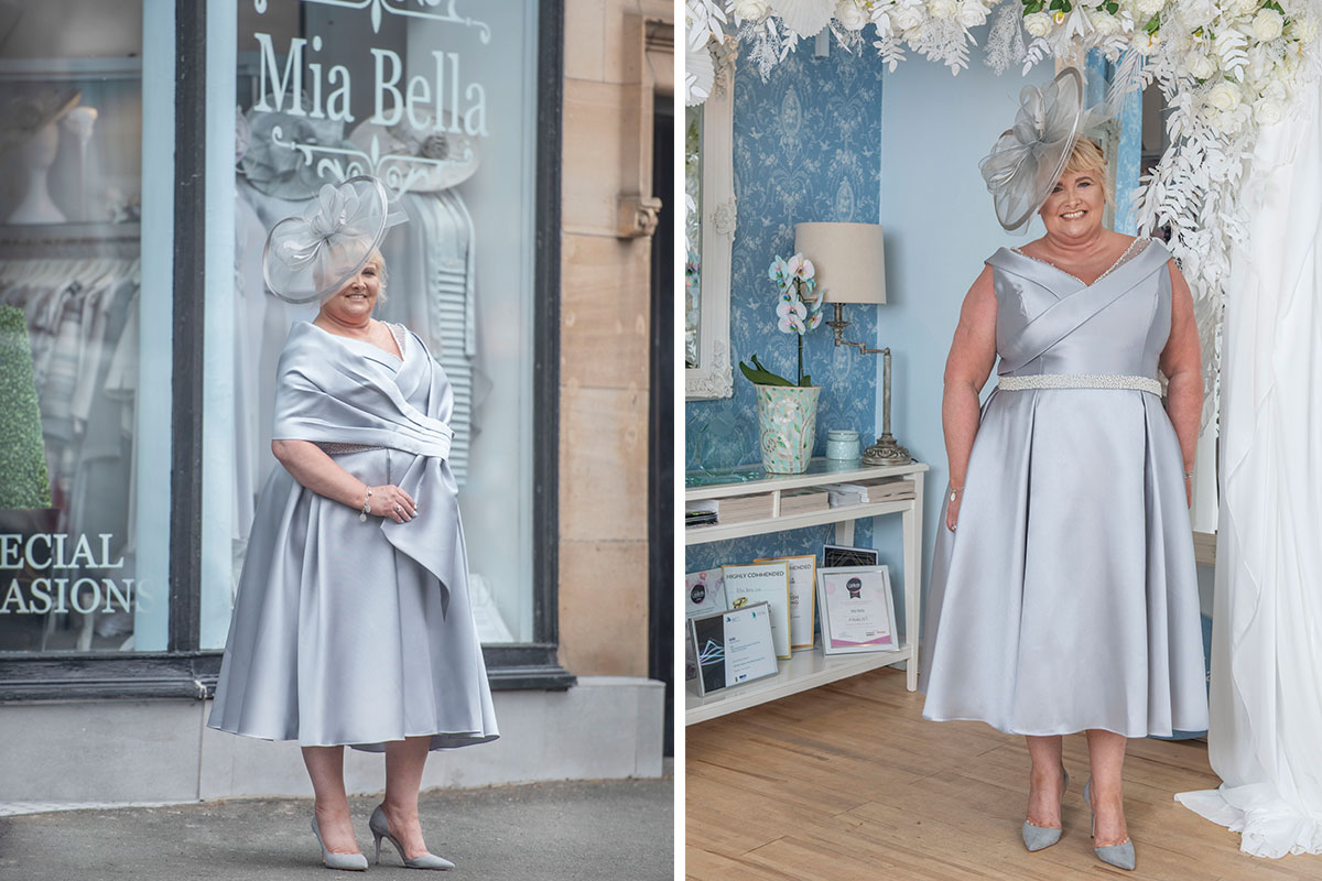 A lady wearing a silver dress and wrap from Mia Bella posing inside and outside the shop