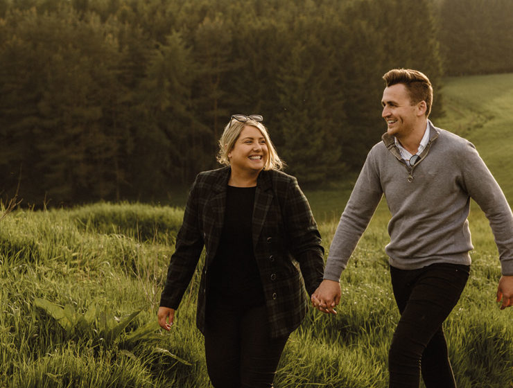 smiling male and female couple holding hands walking across a field by Eilidh Sutherland Photography