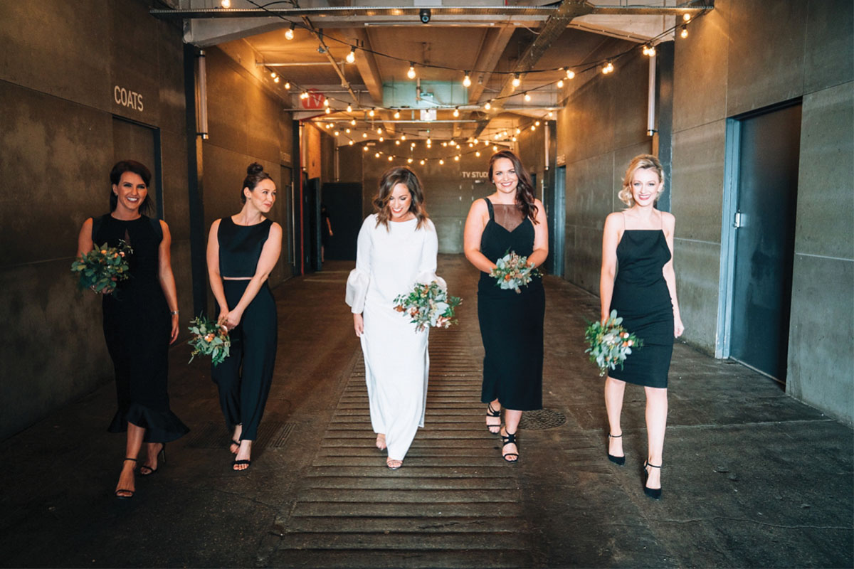 a bride and four bridesmaids wearing black dresses walking in SWG3 in Glasgow