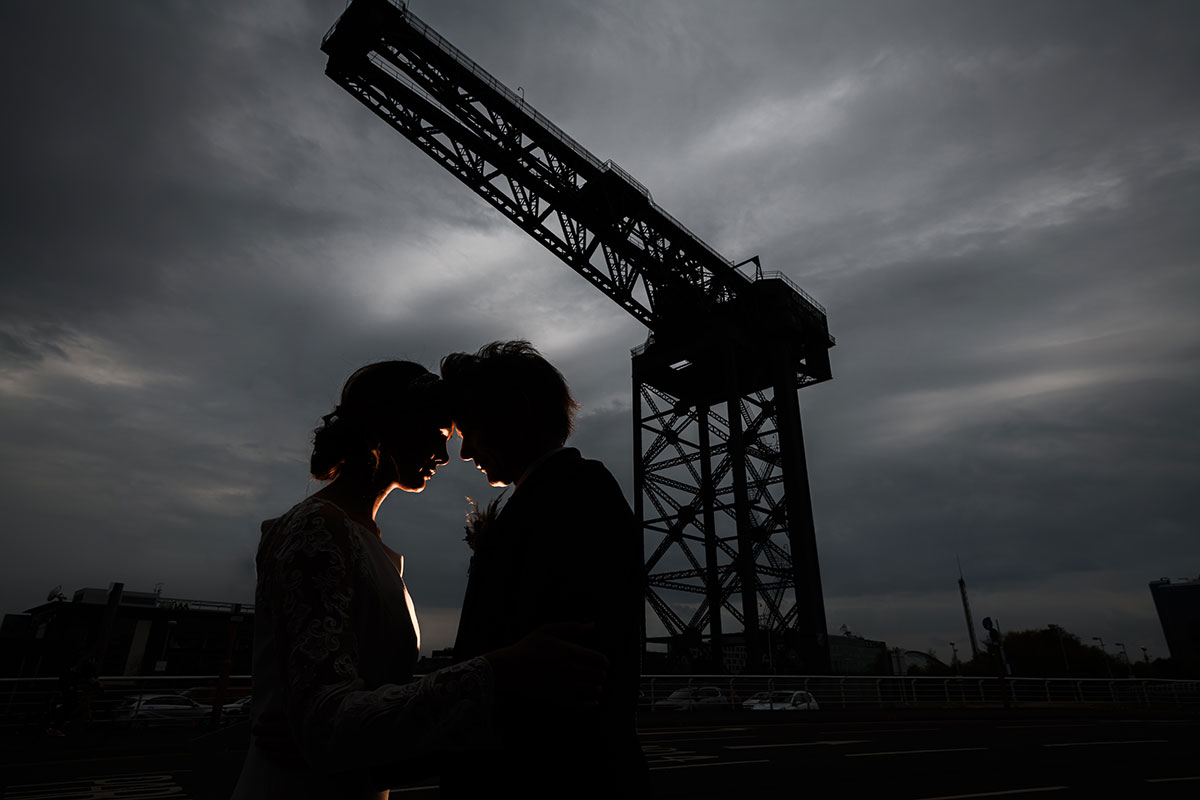 A silhouetted image of two people standing with foreheads touching underneath the Finnieston Crane in Glasgow