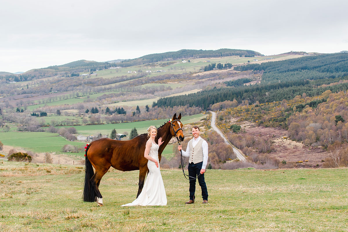 Wedding photo of bride and groom standing in Scottish Highlands countryside with brown horse