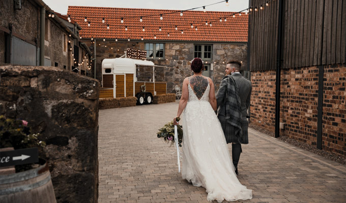 A bride and groom wander through The Den at Culross