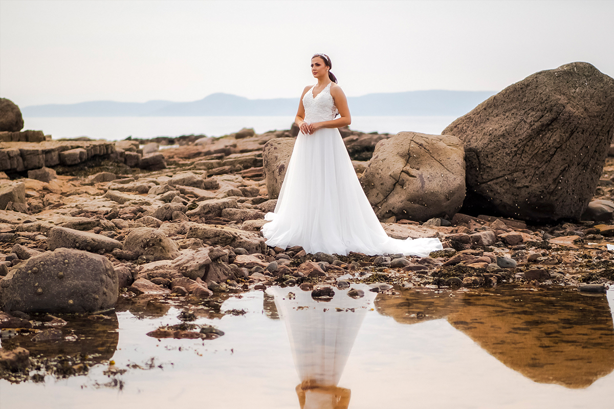 Model in a Dream Brides gown, on the beach