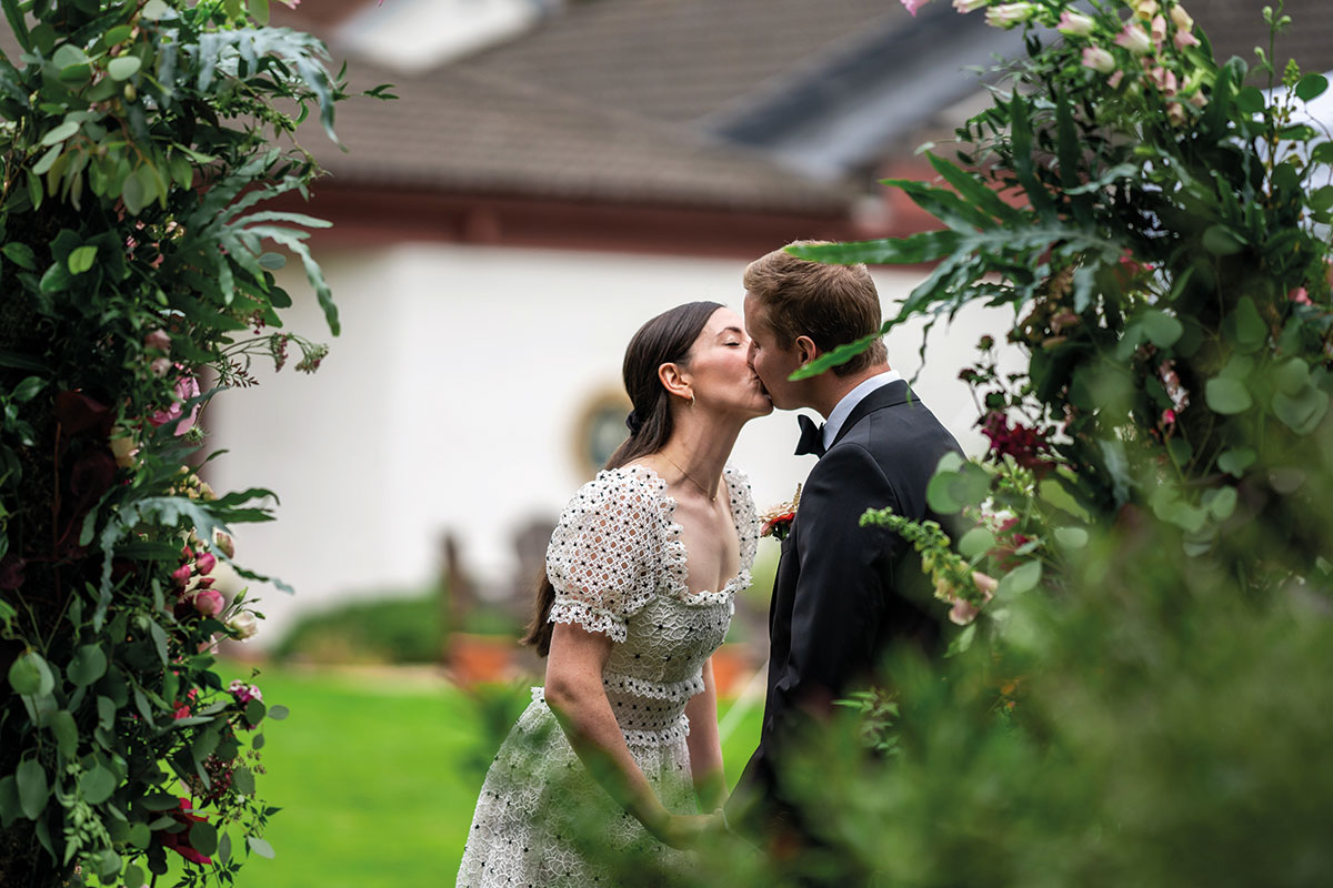 bride kissing groom with greenery at side and in foreground