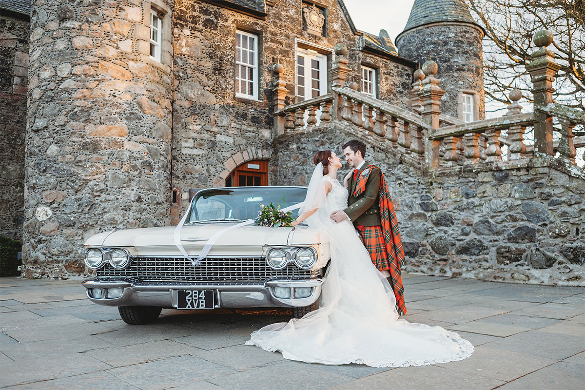 A bride and groom stand in front of a car from American Classic Wedding Cars