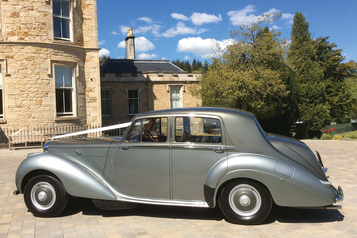 One of MET Wedding Cars' vehicles in front of a venue