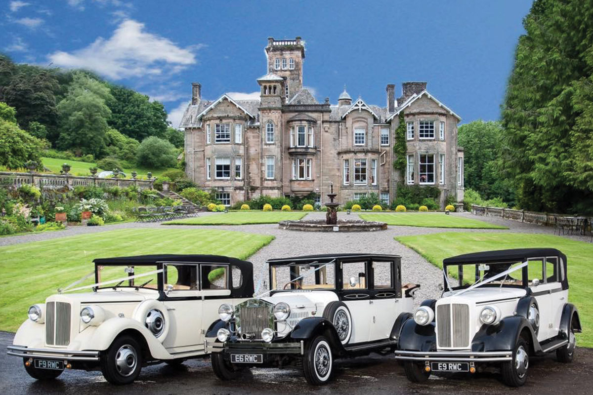 Three vintage wedding cars from Rennick\'s Wedding Cars outside a stately home