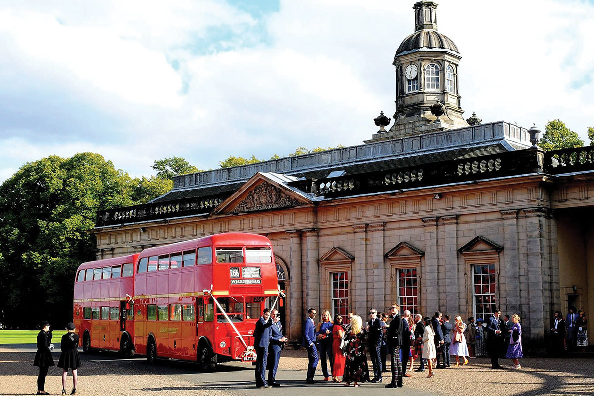 A vintage routemaster bus from The Red Bus outside a wedding venue