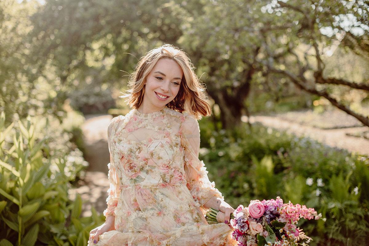 A woman in a floral dress walks in a garden