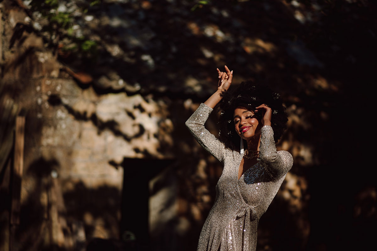 A woman in a sequin dress dances in front of a wall outside