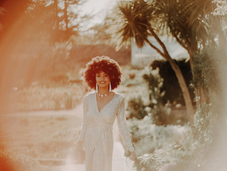 A woman in a sparkly dress walks through a garden with palm trees