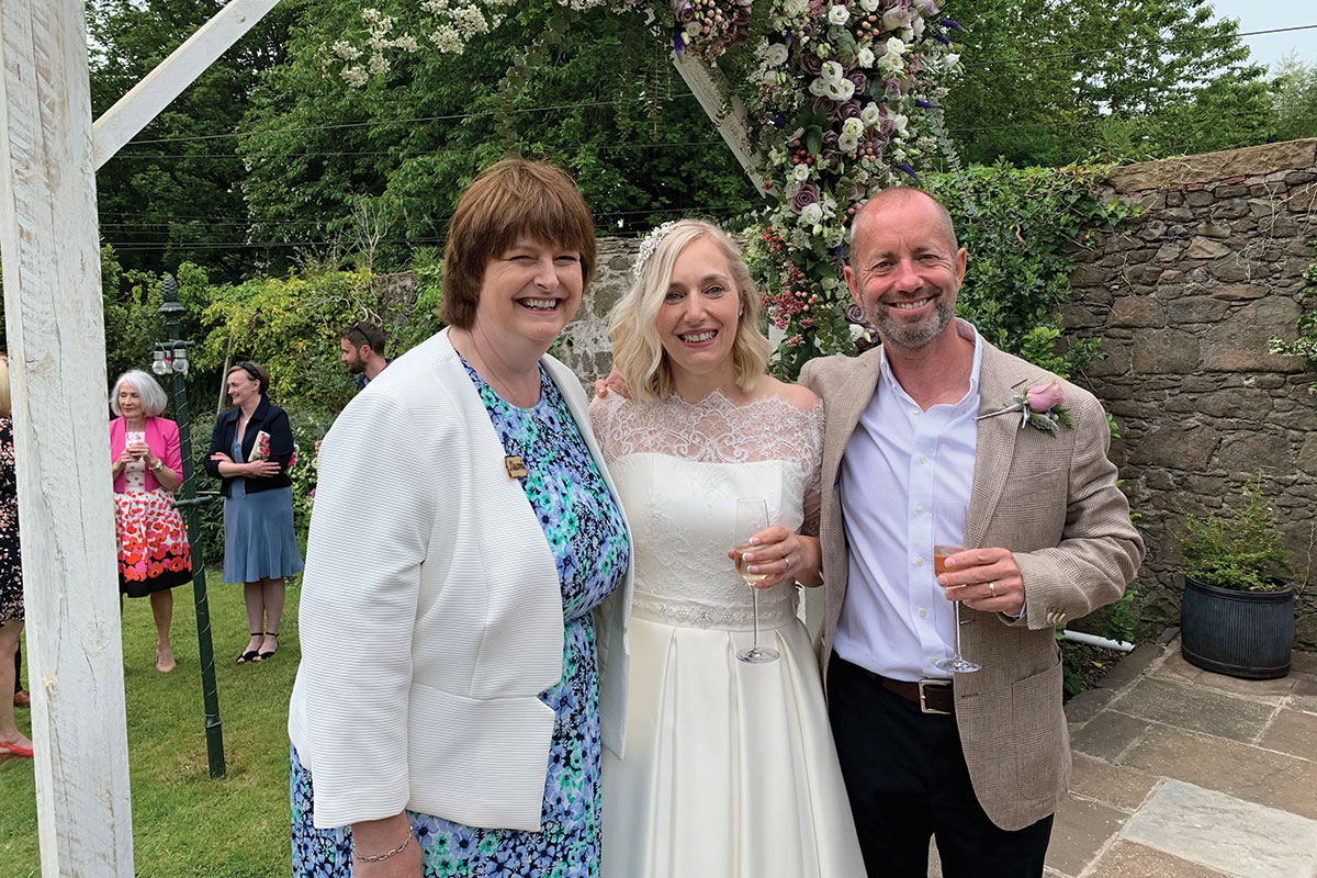 A celebrant poses for a photo with the couple after the ceremony