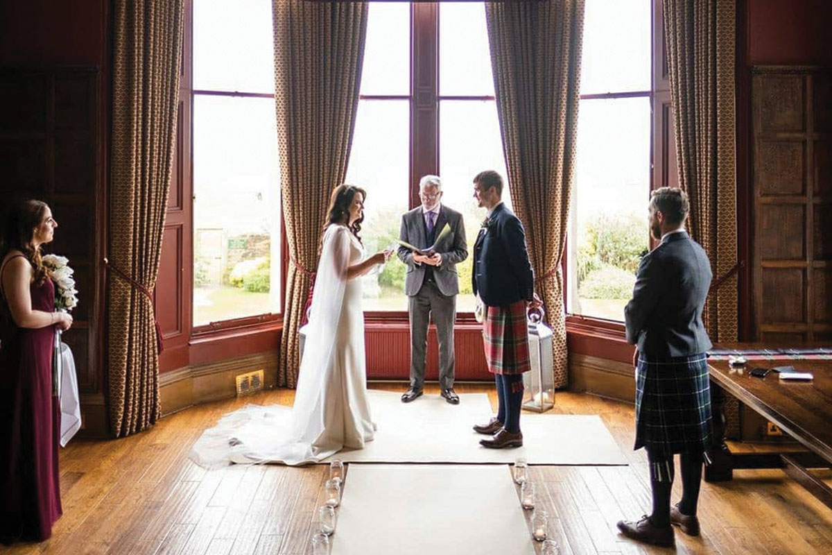 A couple exchanges vows in front of two witnesses in a large room in a stately home