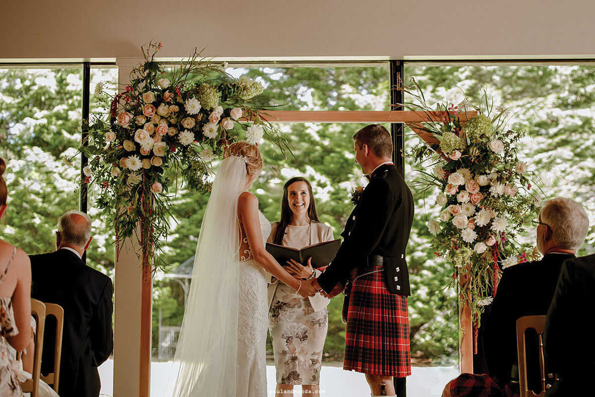 A celebrant and couple stand in front of an arch decorated with flowers during the ceremony