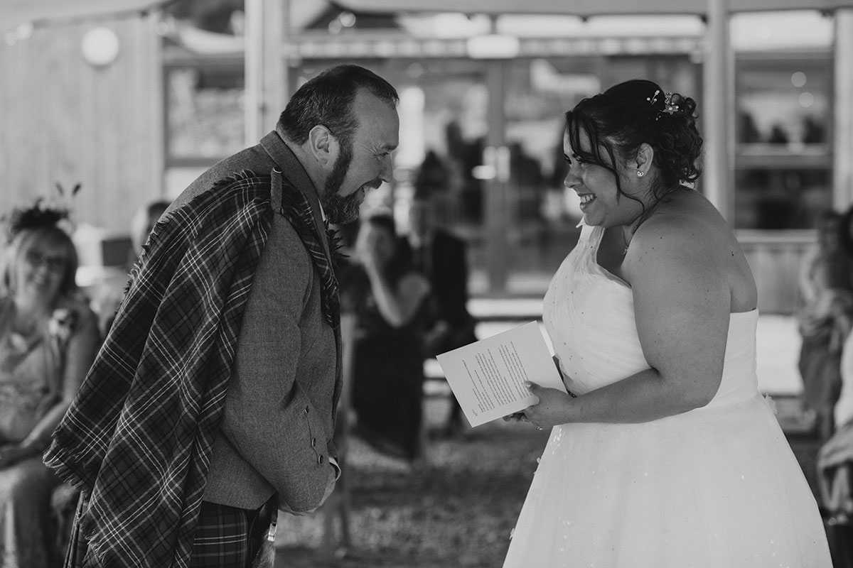 A black and white image of a couple exchanging vows