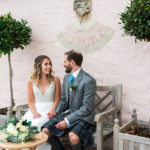 smiling bride and groom sitting on a bench outside Buittle Castle