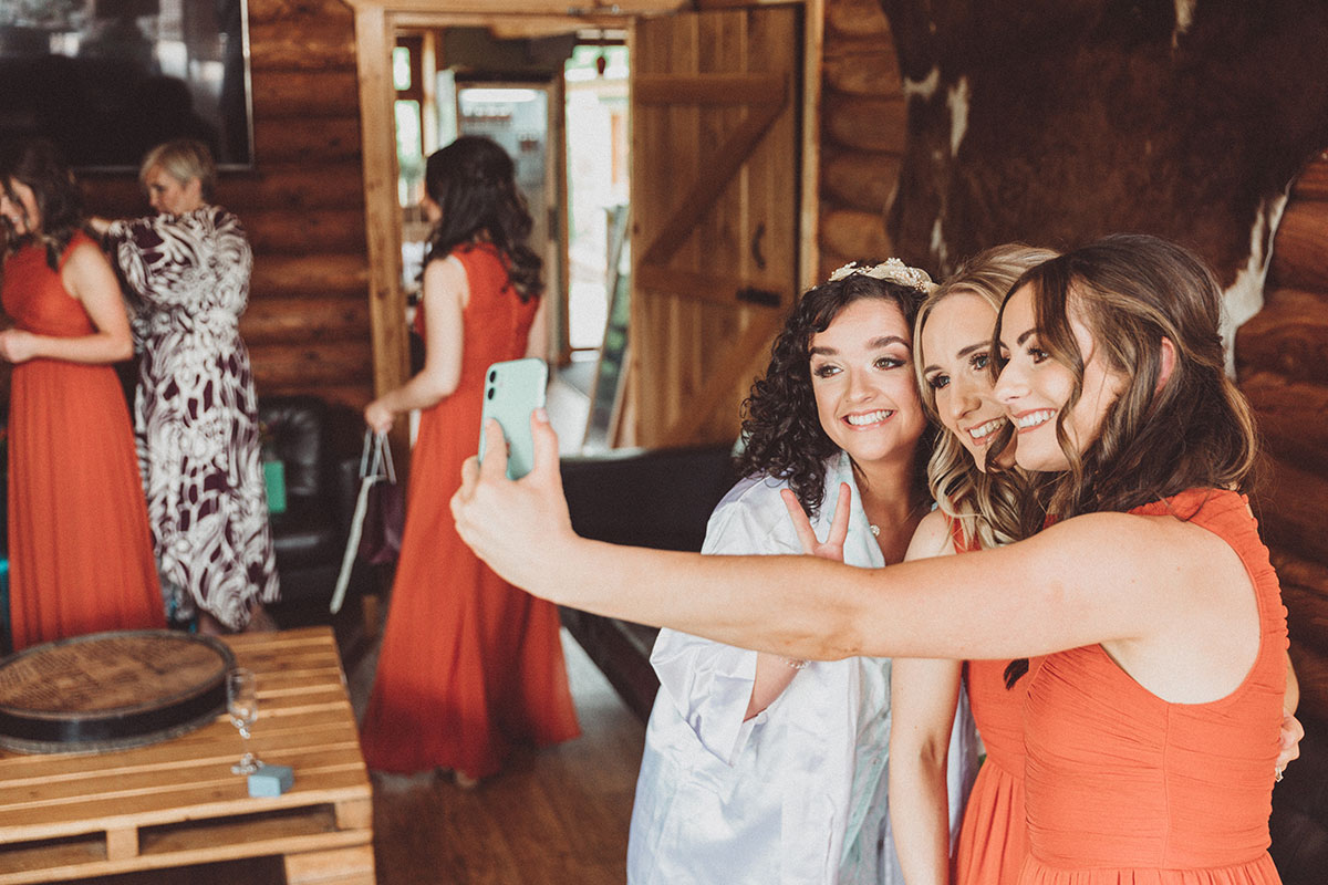 a bride and two bridesmaids wearing orange take a selfie