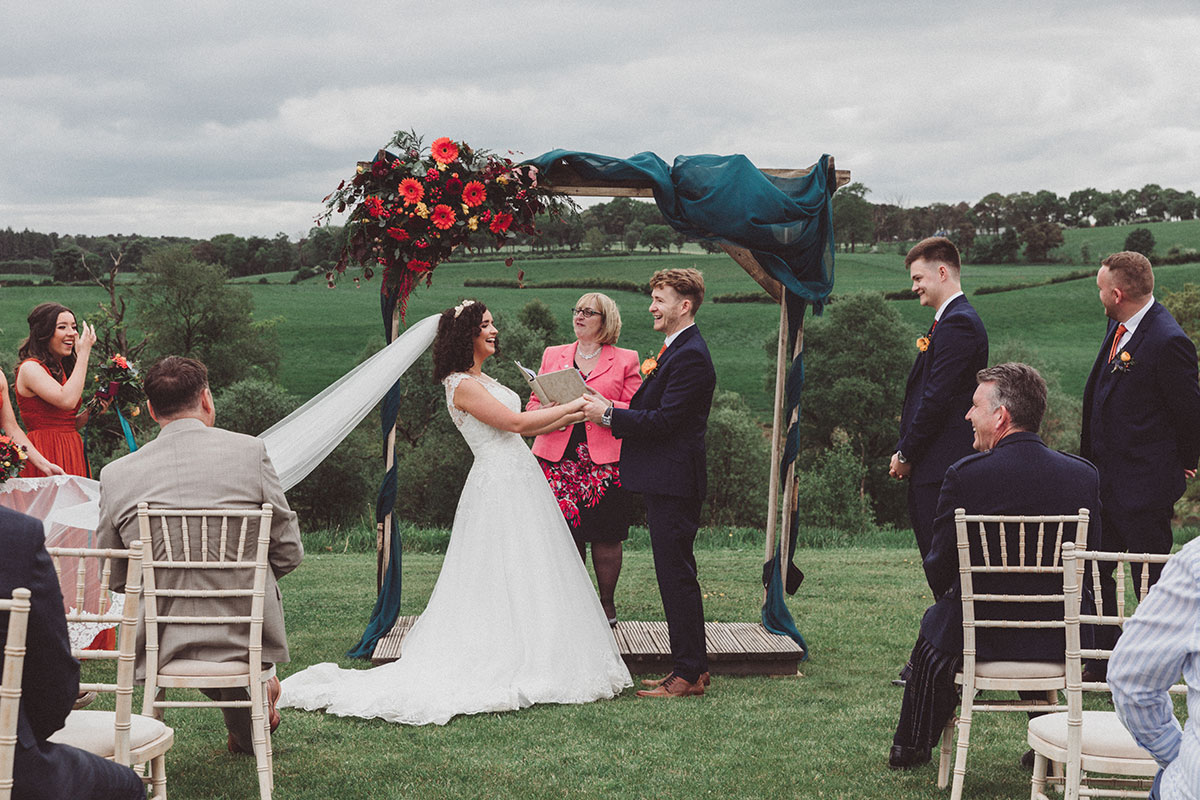 bride and groom holding hands in front of ceremony arch at outdoor wedding ceremony at Eden Leisure Village