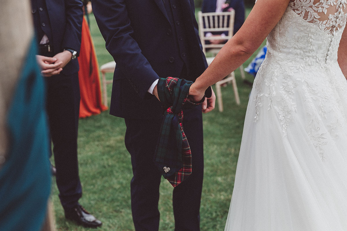 hands of a bride and groom doing a handfasting