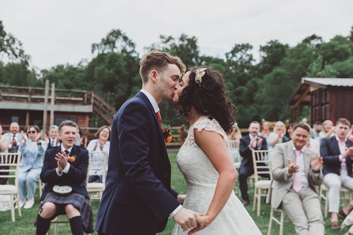 a bride and groom kissing while guests cheer at outdoor wedding ceremony at Eden Leisure Village