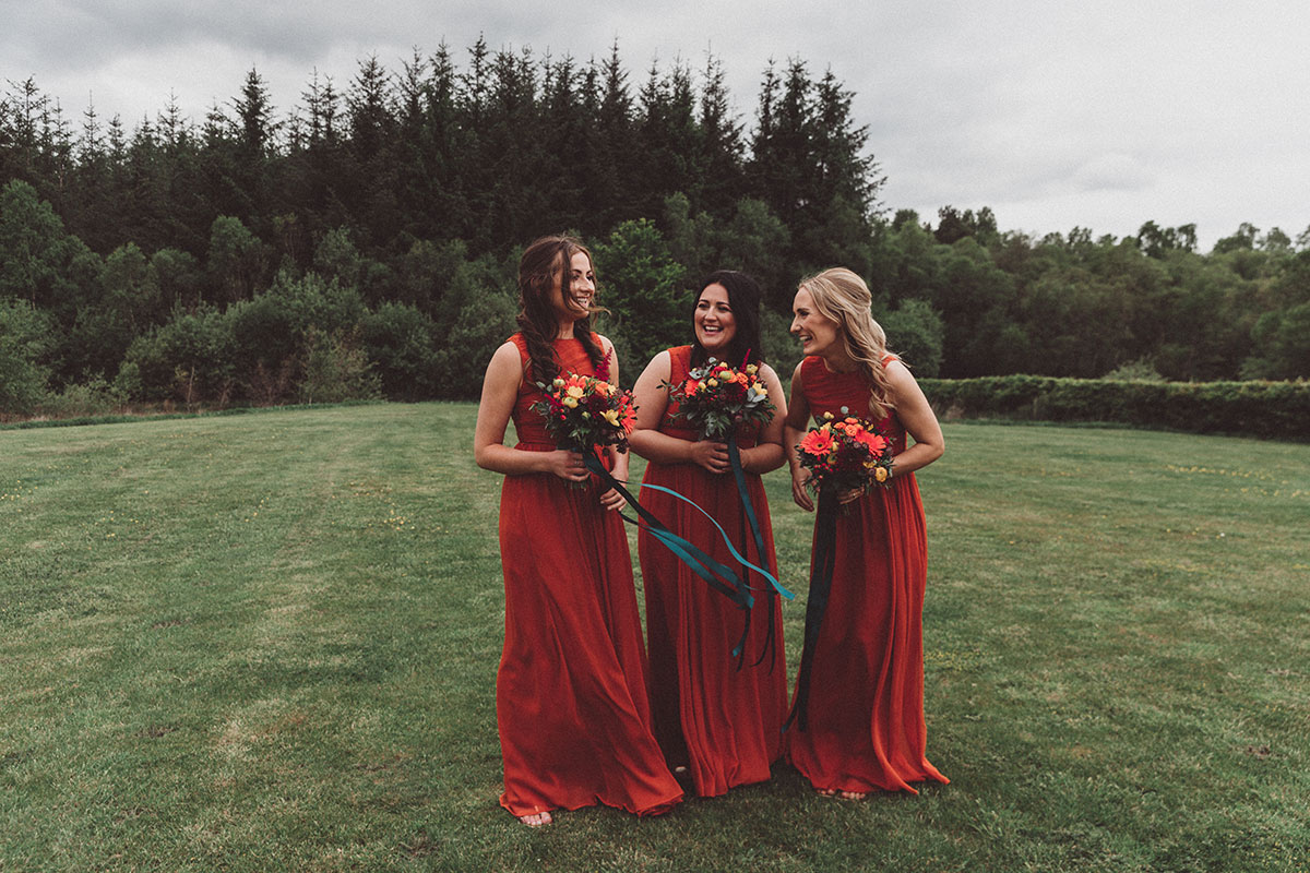 three laughing bridesmaids wearing deep orange and carrying autumn tones bouquets