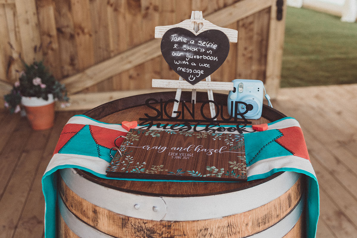 wedding guest book sitting on top of a barrell with chalkboard sign and handmade Sri Lankan table runner