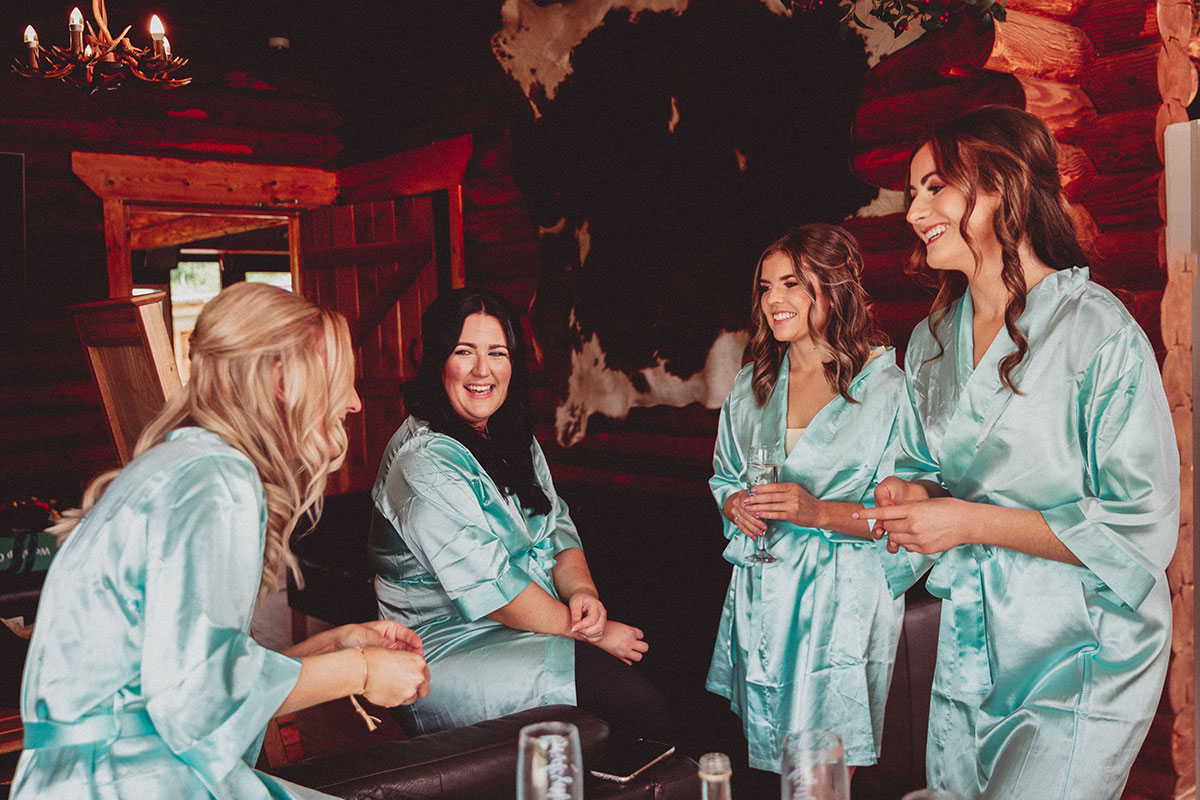 our bridesmaids laughing wearing pale blue silk robes