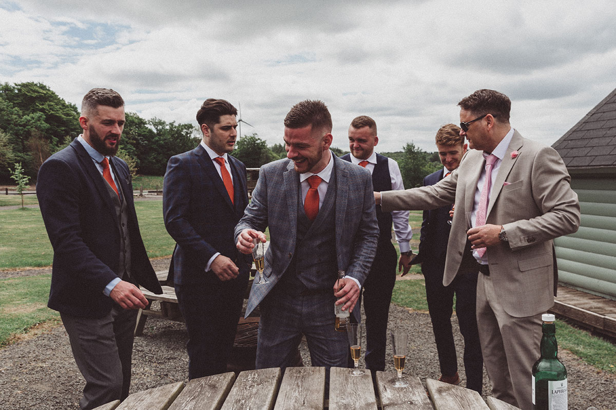 groom and groomsmen outside at Eden Leisure Village drinking beer and fizz