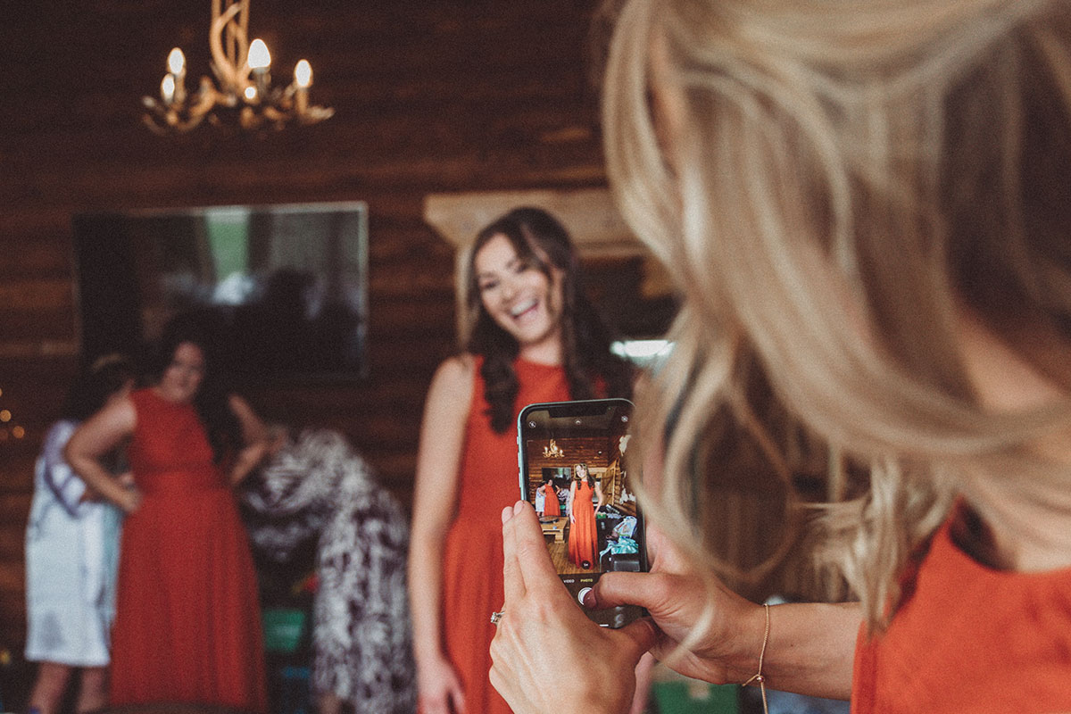 bridesmaid wearing orange taking a picture of another smiling bridesmaid