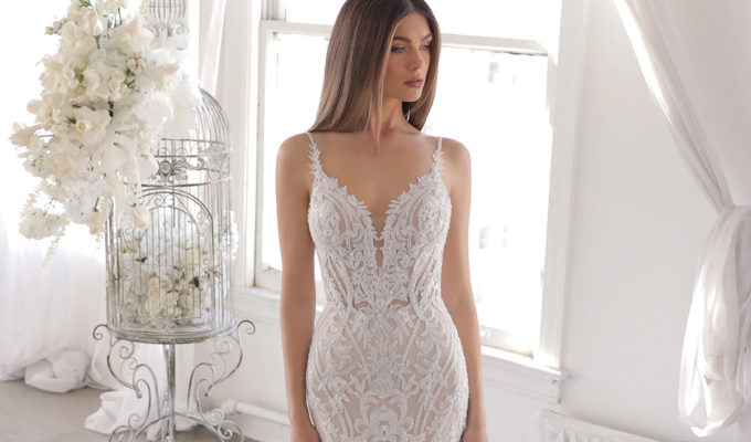 Model wearing Onelia lace wedding dress by Blue by Enzoani from Kudos Bridal Boutiques in Dunfermline with a bird cage filled with flowers in the background
