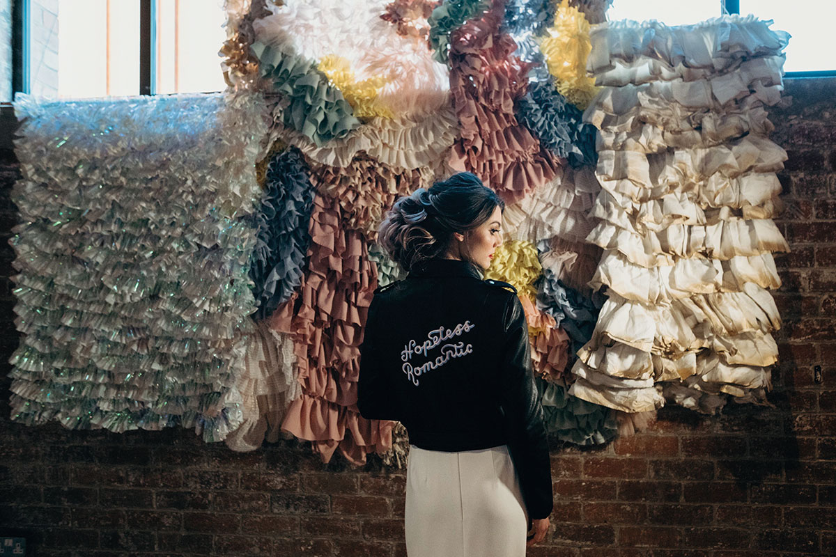 Bride wearing Hopeless Romantic leather jacket standing in front of frilly wedding wall hanging by Frill Factory
