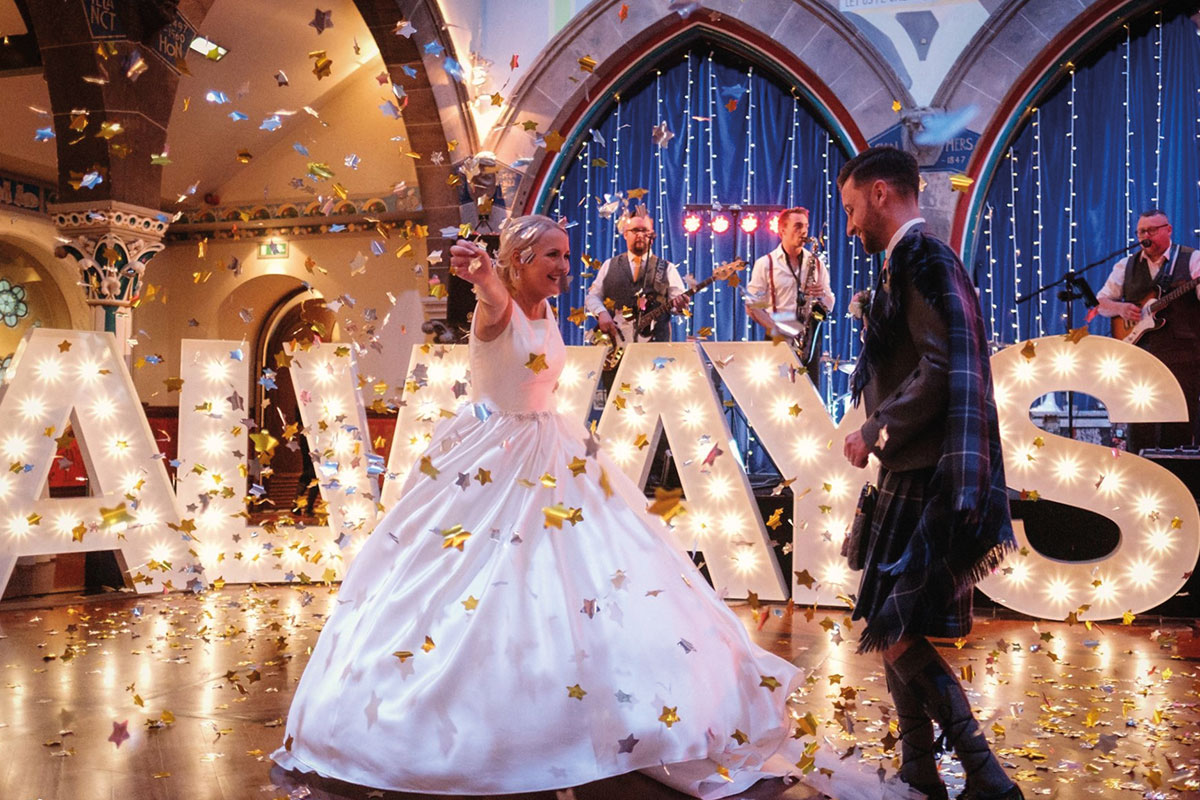 A bride and groom dancing in front of ALWAYS light up letters by Big Bright Letters