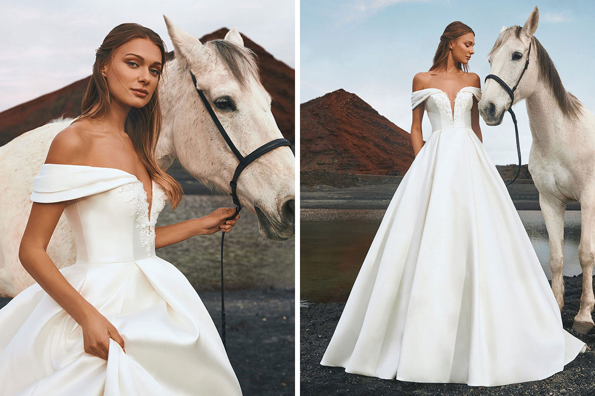 Bride standing with a white horse wearing a Pronovias wedding dress from Opus Couture