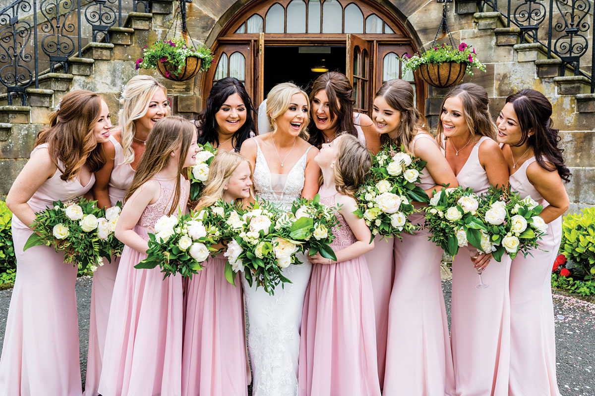 A smiling bride surrounded by ten bridesmaids wearing pink at Dalmahoy Hotel and Country Club